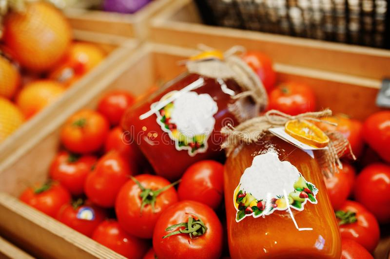 Colorful shiny fresh vegetables. Tomatoes with canning hommemade and handmade tomato juice on the shelf of a supermarket or. Grocery store stock photography