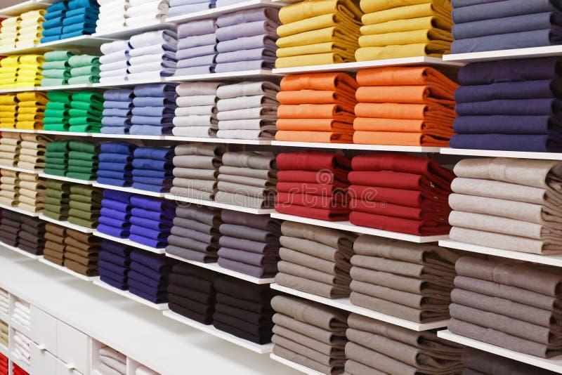 Colorful shirts insade fashion store shelves. Colorful shirts arranged in stacks inside fashion store shelves stock images