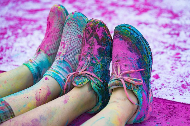 The colorful shoes and legs of teenagers with purple color powder in the public event The Color Run.  royalty free stock images