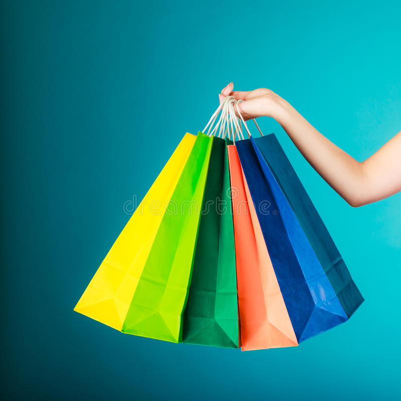 Colorful shopping bags in female hand. Sale retail. Closeup of colorful paper shopping bags in female hand on vibrant blue. Woman girl buying clothes. Sale and stock photography