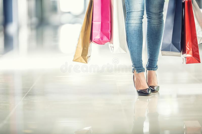 Colorful shopping bags in the hands of a shoppers woman and her legs jeans and shoes royalty free stock image