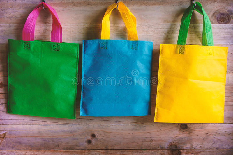 Colorful shopping bags hanging on wooden wall stock photos