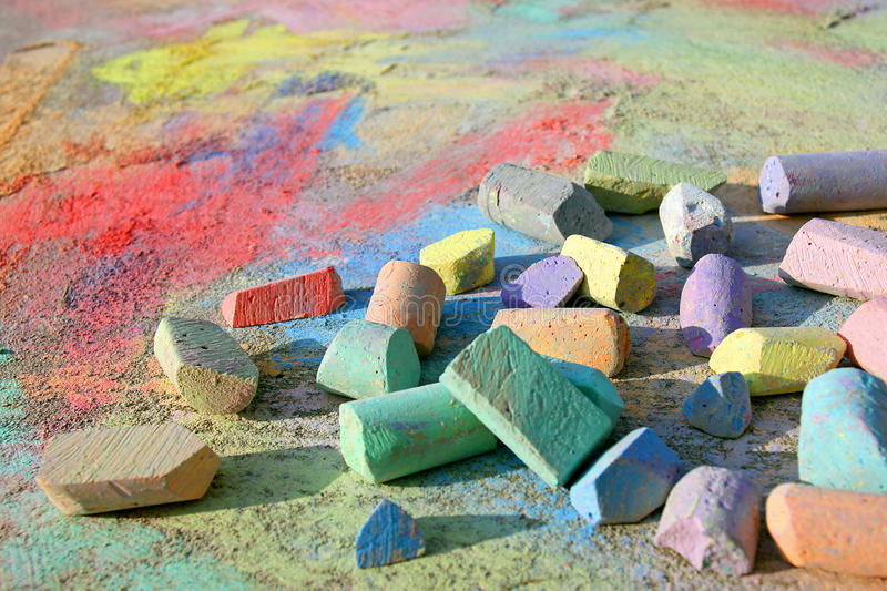 Colorful Sidewalk Chalk. A collection of colorful children's sidewalk chalk is scattered on the pavement, which is colored rainbow swirls royalty free stock photo