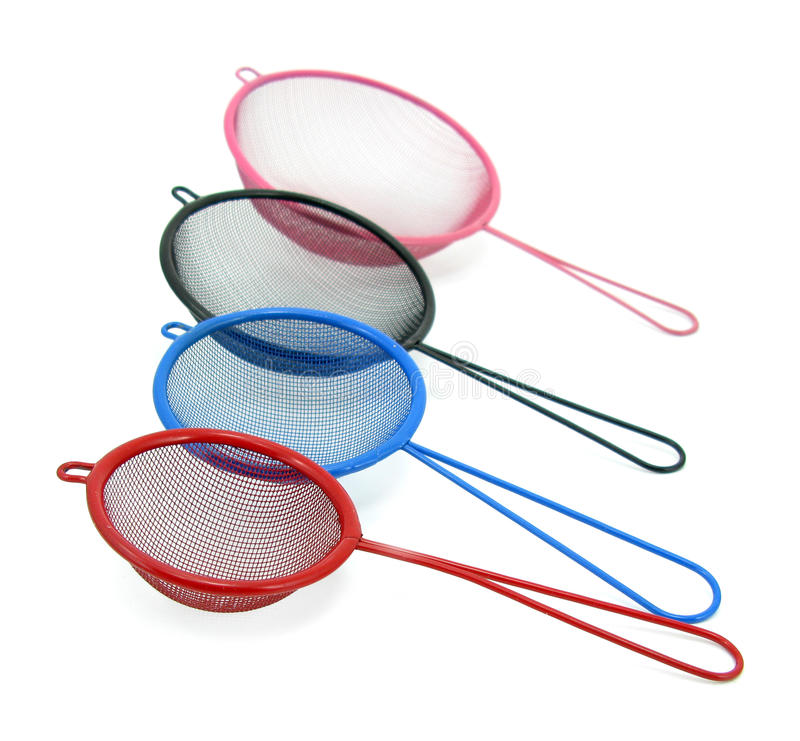 Colorful sieves. Set of four colorful plastic sieves isolated on white background royalty free stock photo