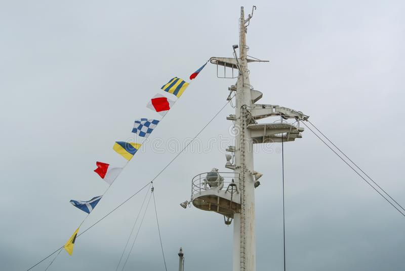 Colorful signal nautical flags against cloudy sky. royalty free stock photo