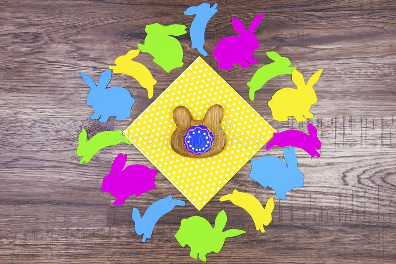 Colorful silhouette of rabbits on wooden background. Happy Easter concept. Wooden eggs stand in shape of rabbit in center on yellow doily surrounded by stock photos