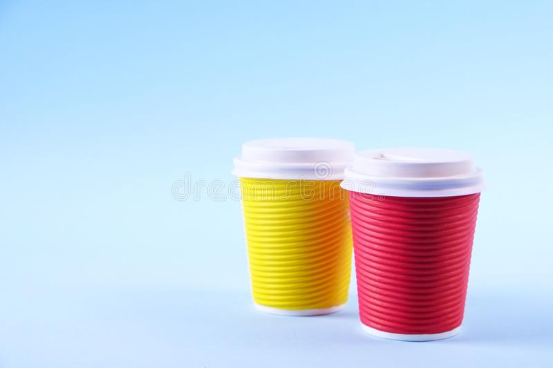 Colorful simplistic minimal composition with heat proof paper coffee cup. Take out tea mug with plastic cap. Coffee shop concept. stock photos