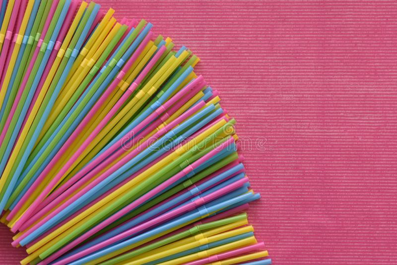 Colorful single use disposable plastic straws in the corner on the pink surface. Colorful single use disposable plastic straws in bright yellow, green, pink and stock photography