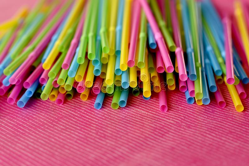 Colorful single use disposable plastic straws on pink surface. Colorful single use disposable plastic straws in bright yellow, green, pink and blue color on the royalty free stock image