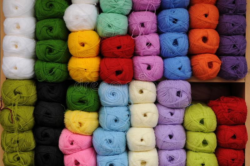 Colorful skeins of wool yarn. Rows of sorted wool yarn . Practical and colorful storage of skeins of yarn used for knitting and crocheting royalty free stock photos