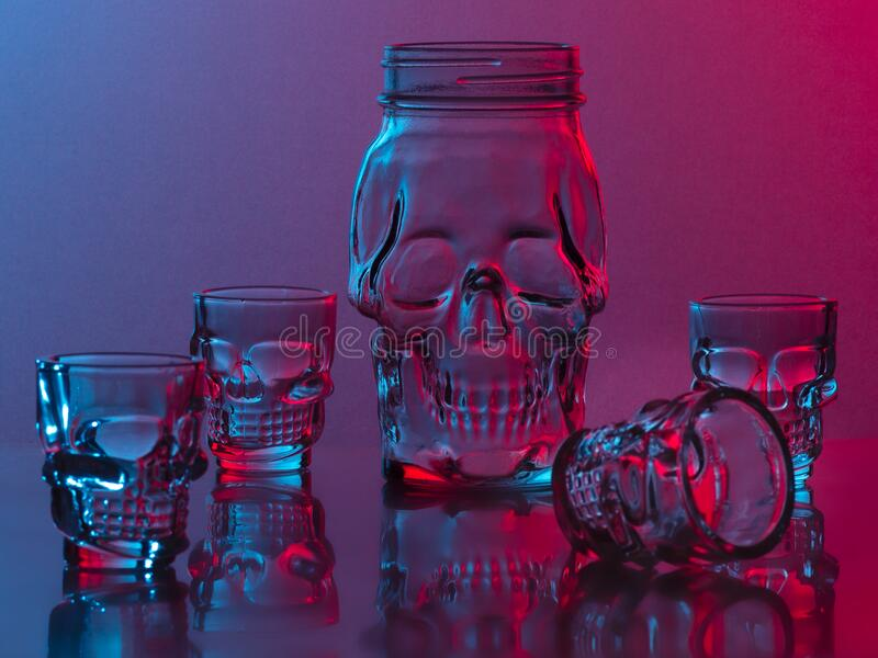 Colorful skulls made of glass. There are glasses and a jar, a photo lit with two lamps stock photo