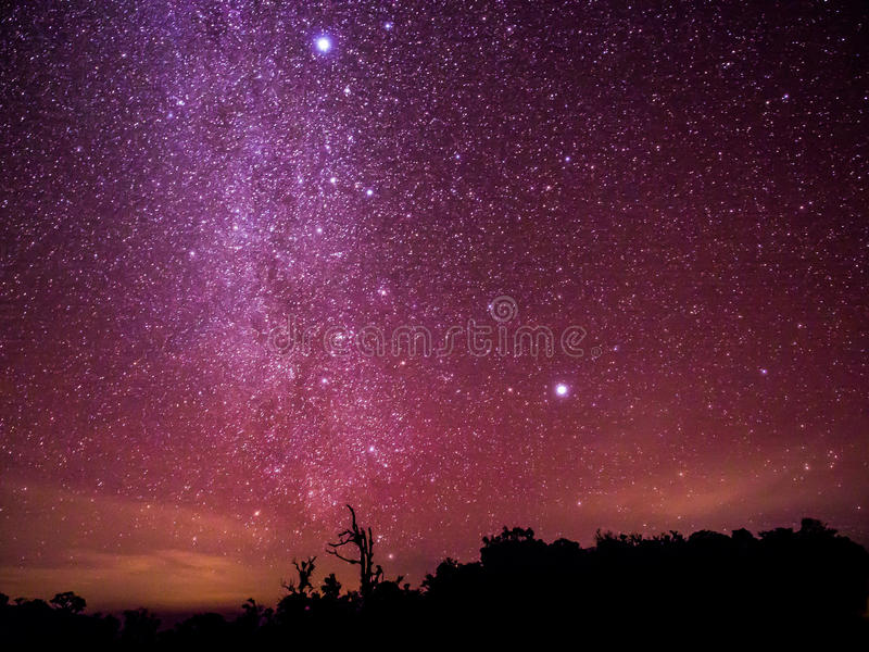 The colorful sky with clusters of stars and milkyway galaxy above the shadow of trees annd mountain, Chiangmai, Thailand. stock photography
