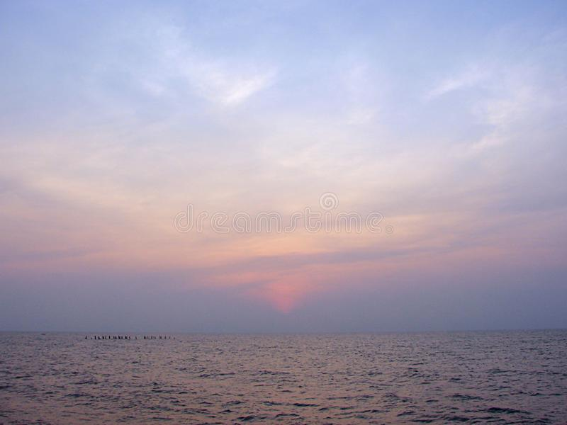 Colorful sky at Dawn at Promenade Beach, Puducherry, India. This is a photograph of colorful sky with clouds over infinite ocean, captured in early morning hours stock photos