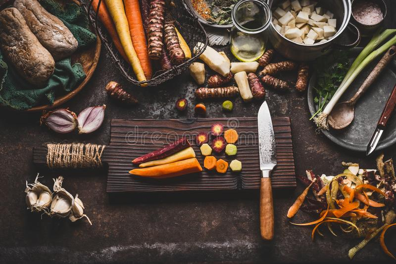 Colorful sliced carrots with knife on wooden cutting board on rustic kitchen table background with root vegetables ingredients for stock photos