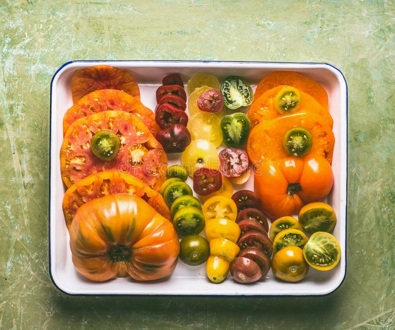 Colorful sliced tomatoes grown in the garden on white tray, top view. The concept of natural vegetables, healthy eating stock photography