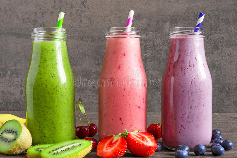 Colorful smoothie drinks in bottles with a straw and fresh fruits and berries stock photos