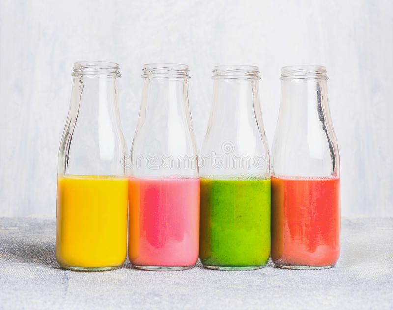 Colorful smoothies assortment in glass bottles on light table, side view. Superfoods and health or detox diet food concept stock photography