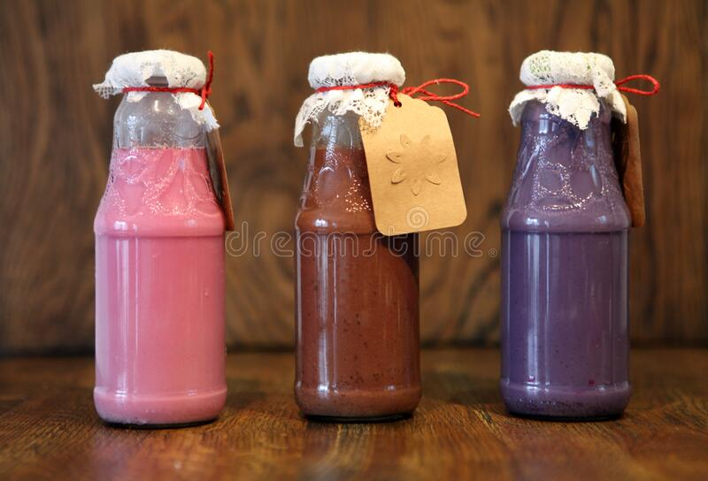 Colorful Smoothies at the bottles. Colorful drink, milk shake in bottle with fresh vegetables and superfoods on a wooden. Colorful Smoothies at the bottles royalty free stock photo