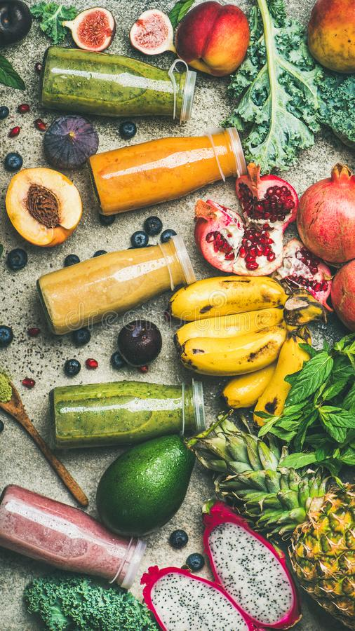 Colorful smoothies in bottles with fresh tropical fruit, top view royalty free stock images