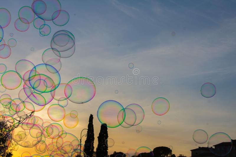 Colorful Soap bubbles against beautiful sunset sky royalty free stock photos
