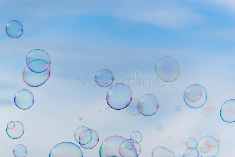 Colorful soap bubbles against blue sky background royalty free stock photos