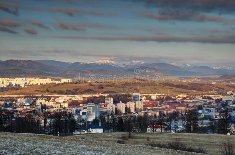 Banska Bystrica cityscape with snowy Low Tatra range Slovakia. Colorful socialist era tower blocks and houses in the outskirts of Banska Bystrica with snow royalty free stock image
