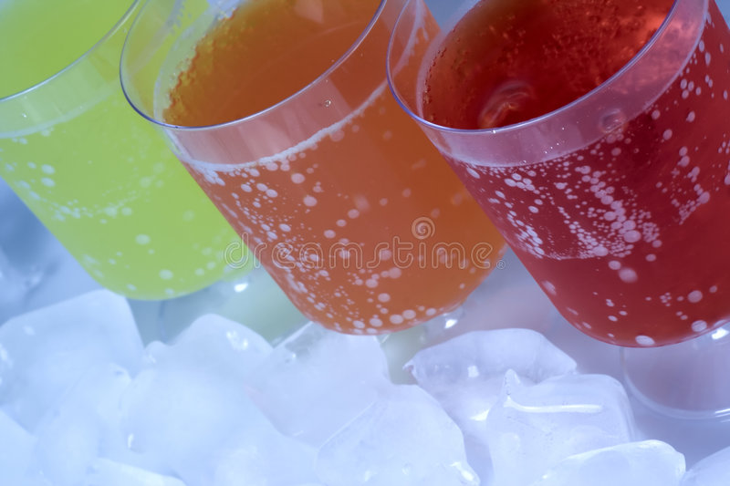 Colorful soda drinks. Row of colorful soda drinks on icy background stock photos