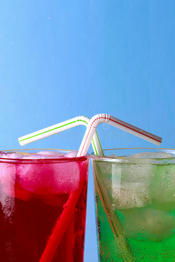 Colorful soda fizzy drinks. Red and green soda fizzy drinks in glasses with ice and straws crossing on a blue background stock image
