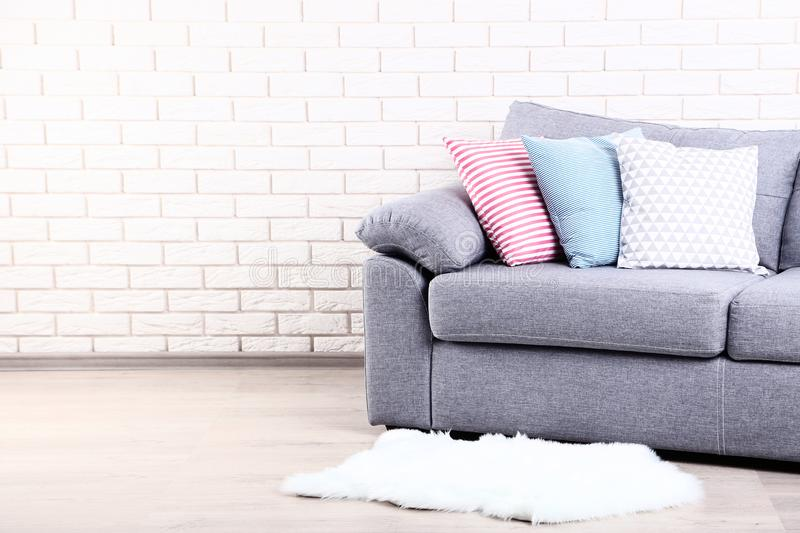 Soft pillows on grey sofa stock photography