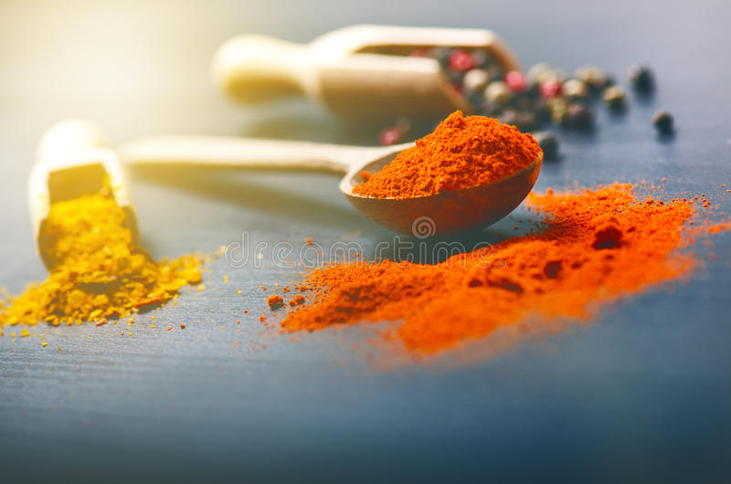 Colorful spices on a dark blue table. Concept of kitchen and cooking. Spicy on a wooden spoon. Colorful spices on a dark blue table. Concept of kitchen and royalty free stock image