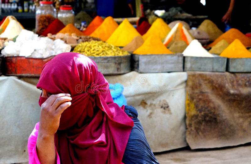 Colorful spices with foreground woman with burqa in the souk of the city of Rissani in Morocco. Rissani`s souk is an authentic market at the doorstep of the stock photography
