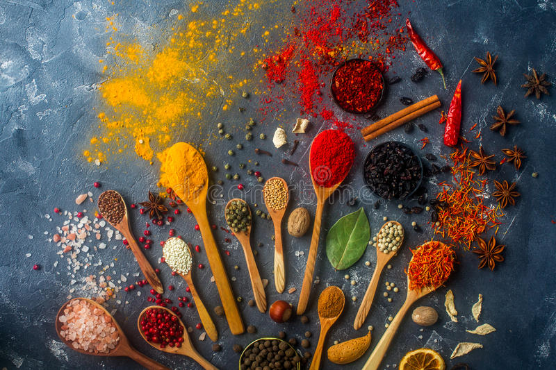Colorful spices in wooden spoons, seeds, herbs and nuts on dark stone table. royalty free stock photography