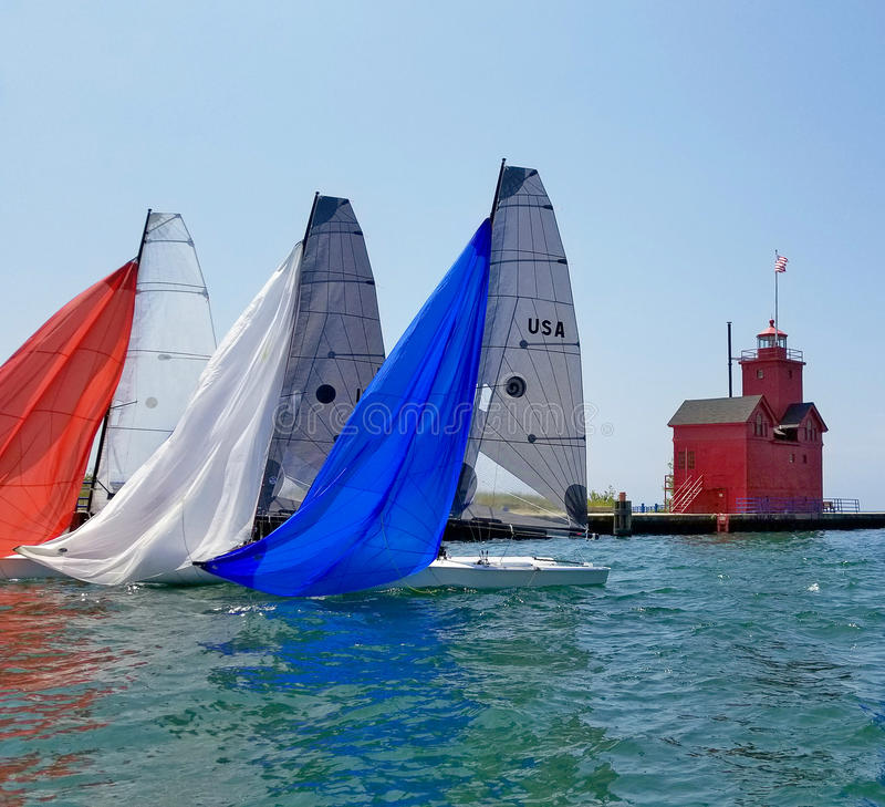 Colorful spinnakers on sailboats in harbor. Red white and blue spinnakers on sailboats in Michigan harbor with red lighthouse on pier royalty free stock photo