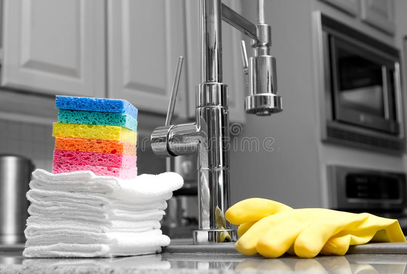 Colorful sponges and gloves in kitchen. Colorful sponges, cloths, and yellow gloves in modern kitchen - housework stock photography