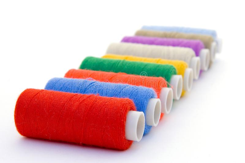 Nine brightly colored spools of threads for sewing stock photo