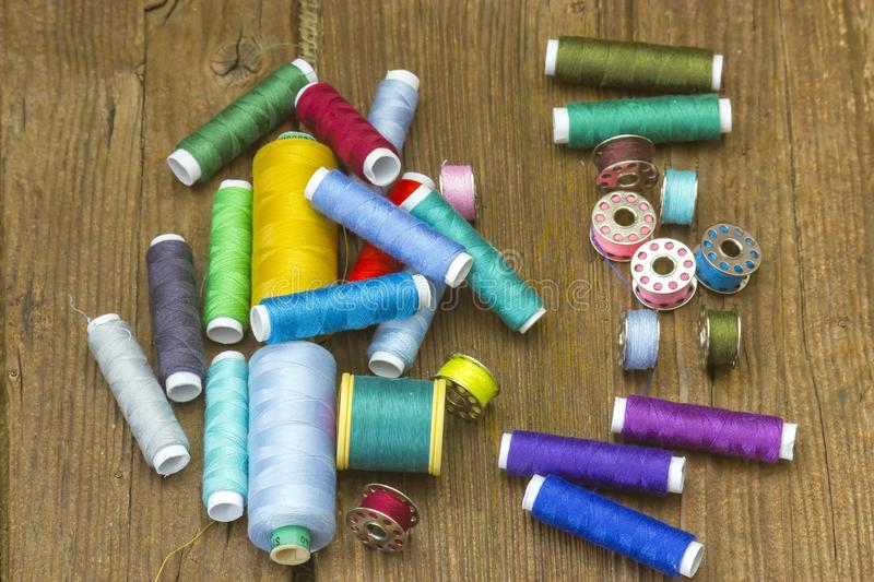 Spools of thread on a wooden background. Colorful spools of thread on a wooden background royalty free stock photos