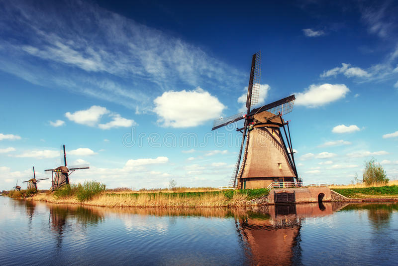 Colorful spring day with traditional Dutch windmills canal in Ro. Tterdam. Wooden pier near the lake shore. Holland. Netherlands stock photo
