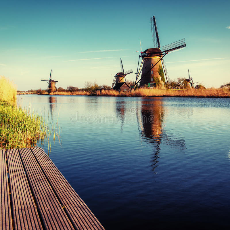 Colorful spring day with traditional Dutch windmills canal in Ro. Tterdam. Wooden pier near the lake shore. Holland. Netherlands royalty free stock photography