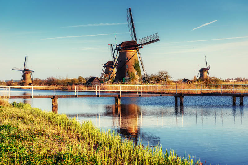 Colorful spring day with traditional Dutch windmills canal in Ro. Tterdam. Wooden pier near the lake shore. Holland. Netherlands royalty free stock photos