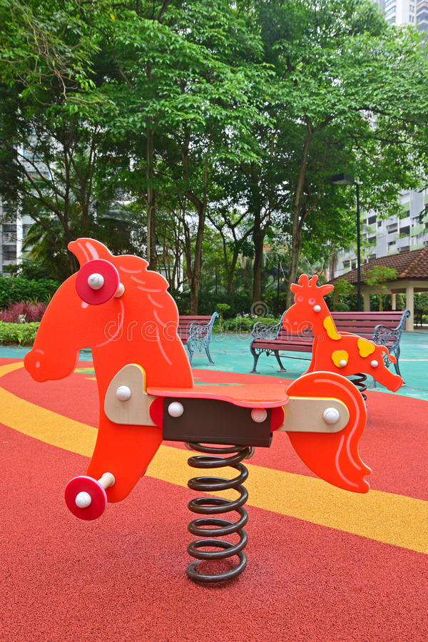 Colorful spring rider in children playground. Colorful spring riders of little pony and giraffe in children playground at a gated community recreational area royalty free stock photos