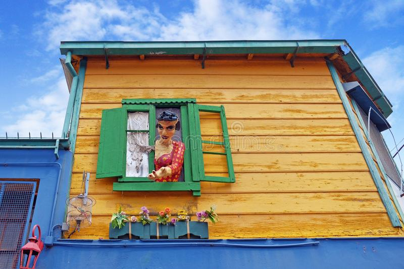 Colorful statue at the green window of a yellow house in the famous Argentinean district La Boca of Buenos Aires against. Colorful statue of a woman at the green royalty free stock image
