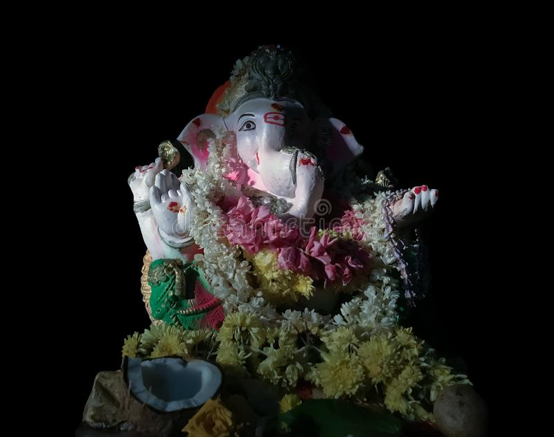 Colorful statue of hindu god Ganesh in black background royalty free stock photography