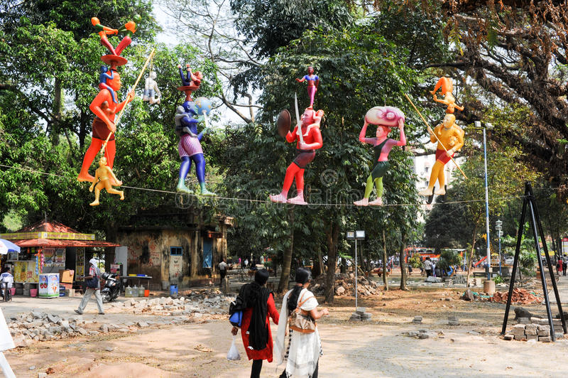 Colorful statues on the central park of Fort Cochin on India. Fort Cochin, India - 16 January 2015: Woman walking onder colorful statues on the central park of stock photos