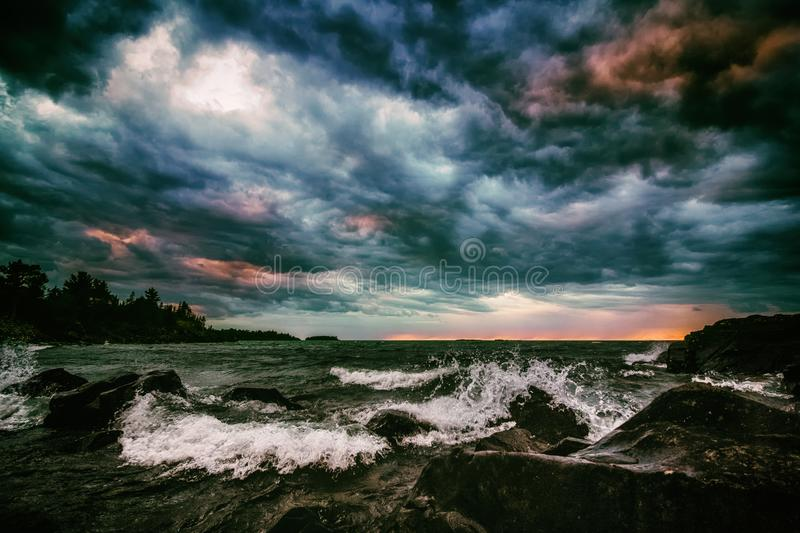 Colorful Storm Clouds Over Turbulent Sea. Dramatic Cloudscape and Seascape Background. stock photo
