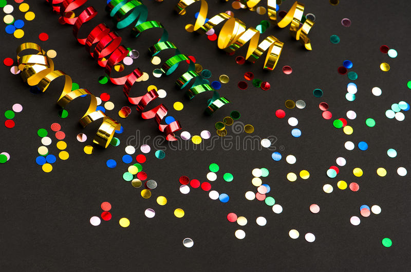 Colorful streamer and confetti. party decoration. Colorful streamer and confetti on black paper background. party decoration stock images