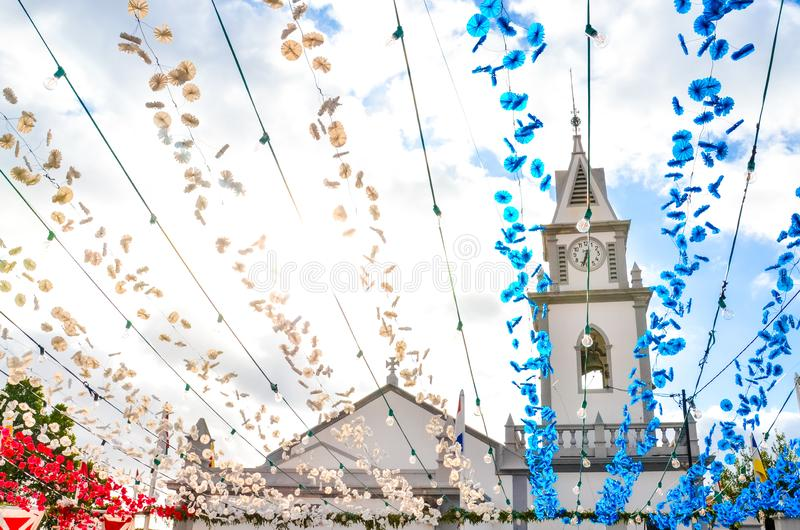 Colorful street decoration hanging on street in Loreto, Madeira, Portugal. Roman Catholic church in the background. Portuguese stock photography