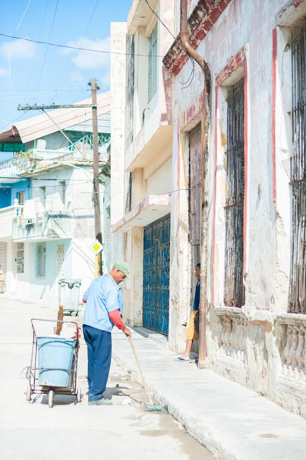 Colorful streets in Cuba. Street lined with colorful crumbling buildings in Havana, Cuba. A worker sweeps and cleans the streets royalty free stock photo