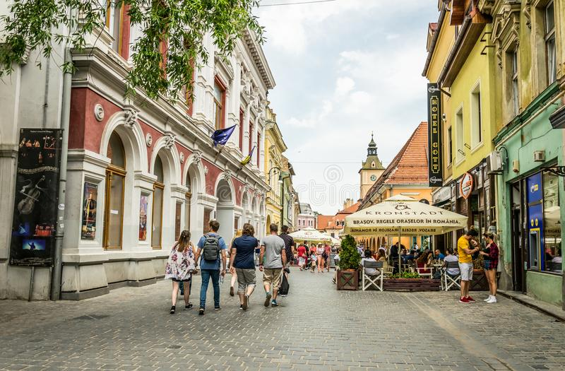 Colorful streets of the medieval European town of Brasov in Romania and cheerful tourists royalty free stock image