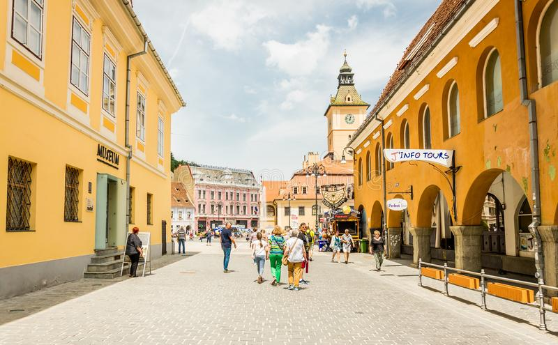 Colorful streets of the medieval European town of Brasov in Romania and cheerful tourists stock image