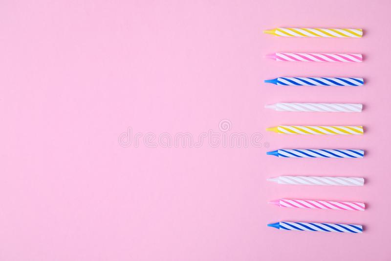 Colorful striped birthday candles on pink background, flat lay. stock images
